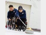 휠체어컬링 리드 포지션의 방민자 선수가 투구하고 있다.  휠체어가 움직이지 않도록 동료 선수가 뒤에서 잡아주는 게 원칙이다. [지호영 기자]