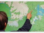 강원 철원군 철원읍 부동산뉴스의 손모 대표가 철원군 지도를 보며 화살머리고지와 철원역 신설 예정 지역 등에 대해 설명하고 있다. [박해윤 기자]