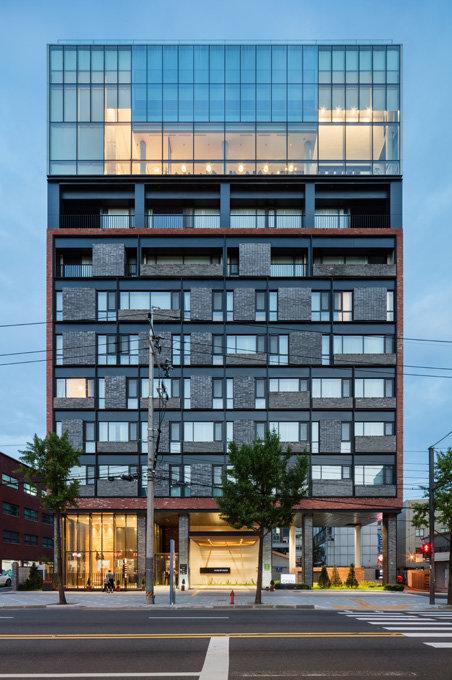 핸드픽트 호텔의 야경. 7층까지는 붉은 벽돌로 박스를 치고 검은색 철판으로 안정감을 부여하면서도 유리창과 벽돌의 크기와 형태를 달리해 변화를 줬다. 9, 10층은 반사유리로 박스를 쳐 멀리서 볼 때 화려한 빛을 발하게 했다.[신경섭 제공]
