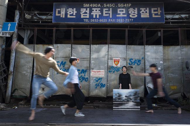 철공소를 배경으로 즉석 연기를 펼치고 있는 예술가들.
