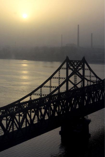 2016년 3월 6일 중국 단둥시 인근에서 바라본 압록강대교와 북한 신의주 공장 위로 태양이 떠오르고 있다. [뉴시스]