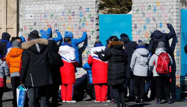 2월 5일 평창선수촌에서 열린 평창올림픽 휴전벽 제막식에서 원길우 북한 선수단장을 비롯한 선수단이 서명하고 있다.