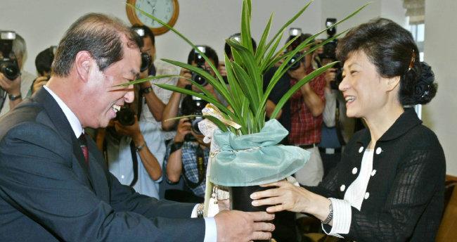 2004년 7월 20일 당시 김병준 대통령비서실정책실장이 박근혜 신임 한나라당 대표에게 노무현 대통령의 축하난을 전하고 있다. [서영수 동아일보 기자]