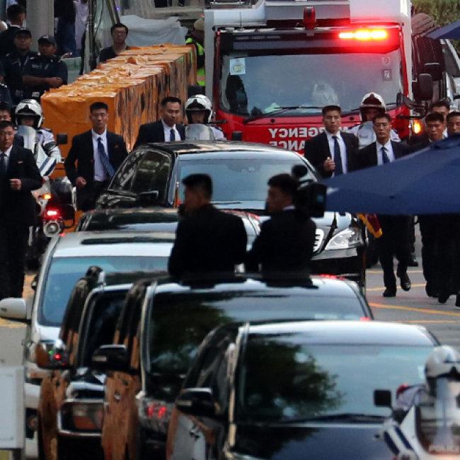 6월 10일 김정은 위원장이 숙소인 세인트레지스 호텔에서 리셴룽 싱가포르 총리와 회담 장소로 이동하기 위해 전용 차량에 오르자 북한 경호원들이 '방탄 경호'를 펼치고 있다.