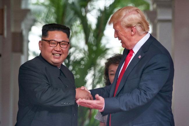 6월 12일 트럼프 대통령이 미소를 지으면서 김정은 위원장과 악수하고 있다.