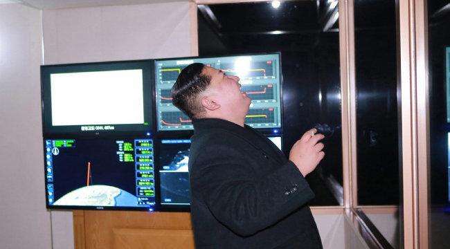 김정은 북한 국무위원장이 2017년 10월 29일 평안남도 평성에서 담배를 든 채 대룩간탄도미사일 시험발사 장면을 지켜보면서 활짝 웃고 있다. [동아DB]