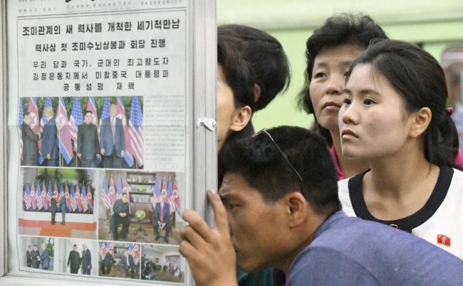 6월 13일 평양 시민들이 김정은 국무위원장과 도널드 트럼프 미국 대통령의 정상회담 소식을 보도한 노동신문을 보고 있다. [AP=뉴시스]