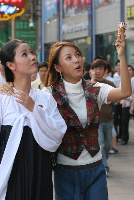 가수 이효리(오른쪽) 씨와 북한 무용수 조명애 씨가 2005년 9월 12일 중국 상하이에서 아이스크림을 먹으며 길거리를 구경하고 있다. [동아DB]