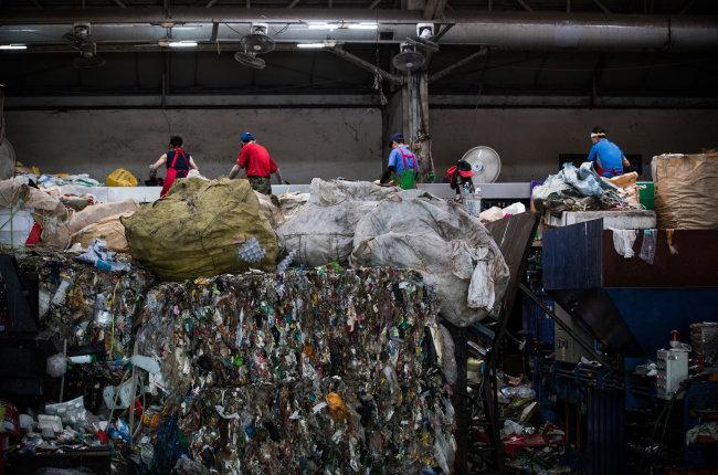 찜통더위는 재활용선별장 작업자들에게 큰 고역이다. 제대로 세척이 안 된 채 배출된 용기에 남은 음식물이 썩는 냄새 때문이다. 악취를 참으며 재활용 가능한 자원을 찾고 있는 작업자들.