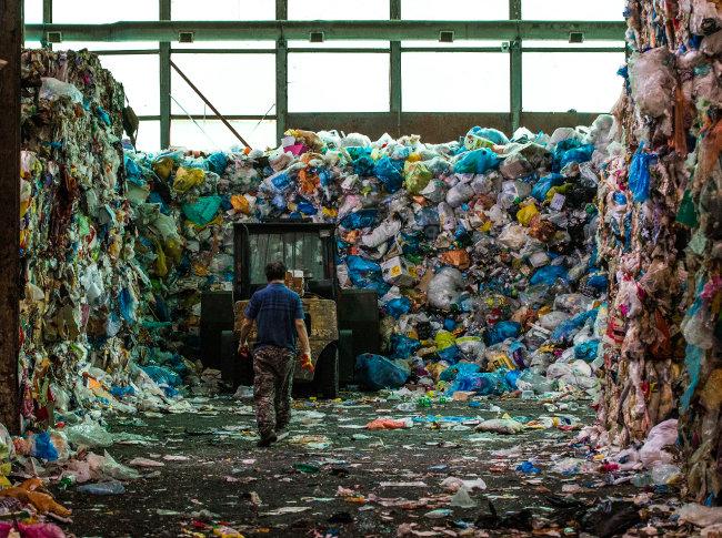 서울 강북에 있는 모 재활용선별장에 들어오는 생활 쓰레기는 하루 50t을 넘는다. 산더미처럼 쌓인 쓰레기를 처리하기 위해 한 작업자가 작업 차량으로 걸어가고 있다.