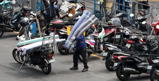 서울 동대문시장 일대에서 퀵서비스 기사들이 오토바이로 배달하고 있다. 지난해에 비해 퀵서비스 매출도 30% 이상 줄어들었다. [뉴스1]