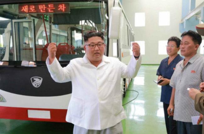 김정은 북한 국무위원장이 8월 4일 북한 기술로 만들었다는 새 버스 앞에 서서 두 손을 들고 있다.[조선중앙통신]
