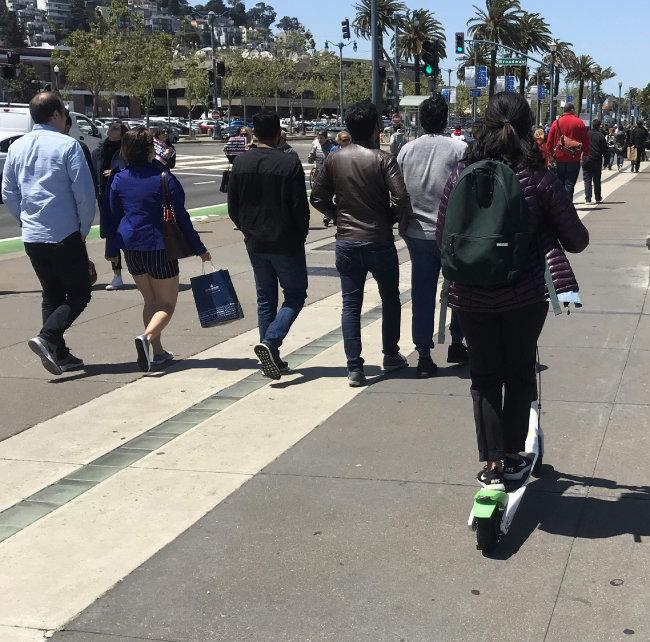 샌프란시스코시의 규제로 영업이 중단되기 전인 5월 샌프란시스코 익스플로러토리엄 근처 보행자 통행로에서 한 사람이 공유스쿠터를 타고 있다. 보행자 통행로에서 공유스쿠터를 타는 건 불법이다.