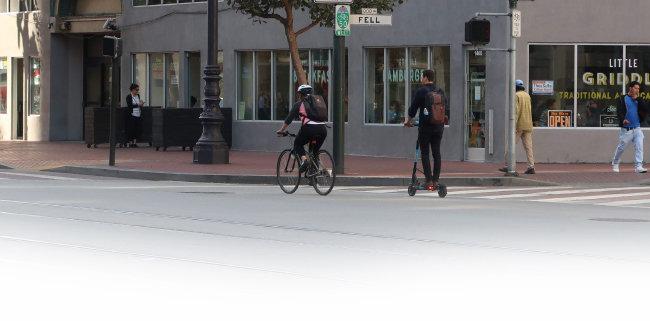 샌프란시스코 마켓스트리트 자전거도로에서 한 청년이 공유스쿠터를 타고 이동하고 있다.