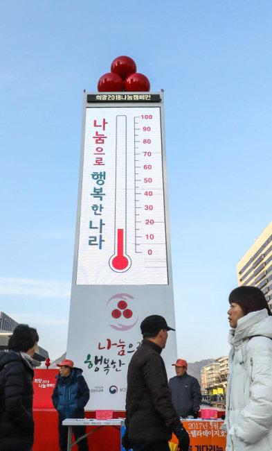 2017년 12월 서울 세종대로 광화문광장에서 시민들이 '사랑의 온도탑' 앞을 지나고 있다. [뉴스1]