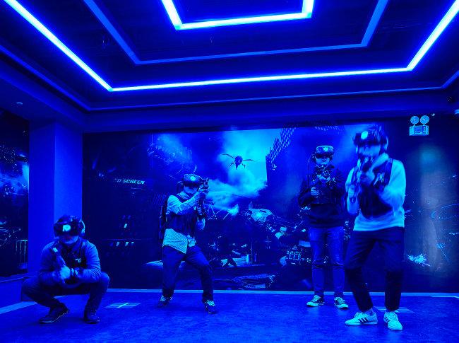 도심형 복합 VR 테마파크 브라이트에서 VR 전투게임을 즐기는 사람들.