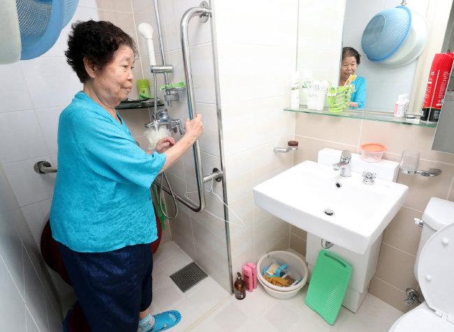 이복순 할머니가 경기 성남시 수정구 위례35단지 자신의 아파트 화장실에 설치된 손잡이를 잡고 서 있다. [최혁중 동아일보 기자]