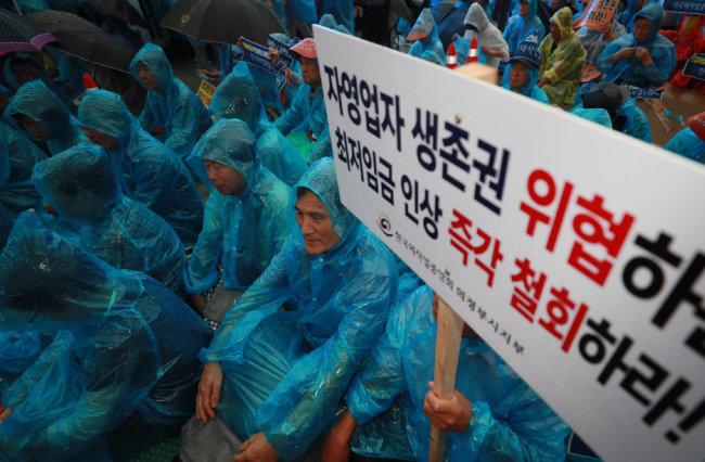 2018년 8월 29일 오후 서울 종로구 광화문광장에서 열린 '전국 소상공인 총궐기' 집회에 참가한 참가자들이 우의를 입은 채 구호를 외치고 있다. [동아DB]