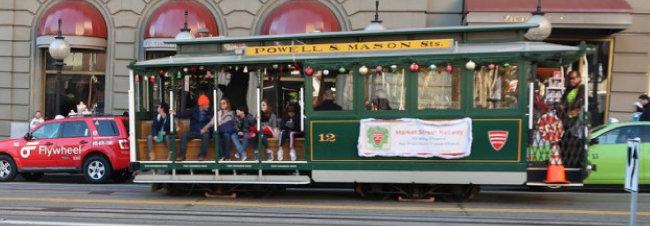 미국 샌프란시스코의 명물 케이블카가 손님을 태운 채 도로에 줄지어 서 있는 택시를 지나쳐 달리고 있다.
