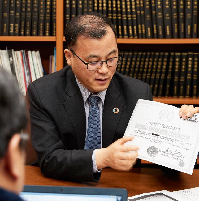 남상민 유엔 ESCAP 동북아사무소 부대표가 위조 유엔친선대사 임명장을 들고 사기 수법을 설명하고 있다. [홍중식 기자]