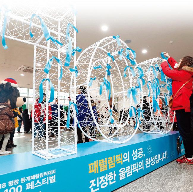 경기 이천 대한장애인체육회 이천훈련원에서 한 시민이 평창동계패럴림픽 G-100 페스티벌에 맞춰 '희망의 리본 달기 행사'에 참여하고 있다.[동아일보]