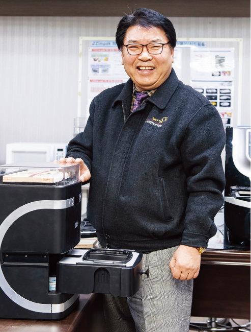 태방파텍이 제조·판매 중인 음식포장기앞에 선 정희국 대표.[홍태식 기자]