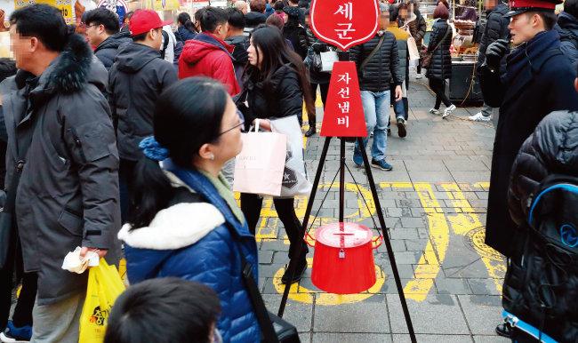서울 중구 명동거리의 구세군 자선냄비. 많은 시민이 자선냄비를 지나치고 있다. [동아일보]