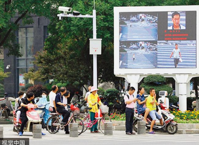 중국 후베이성 샹양시 건널목에서 무단횡단한 주민의 모습이 대형 전광판에 뜨고 있다. [VCG]