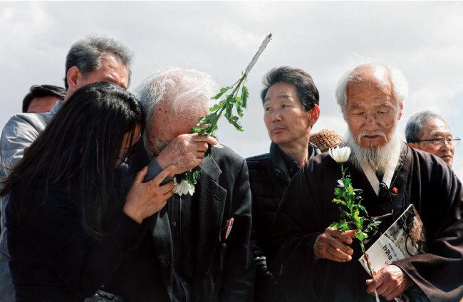 헌화를 하던 추모객이 당시 아픔을 떠올리며 울음을 터뜨리고 있다.