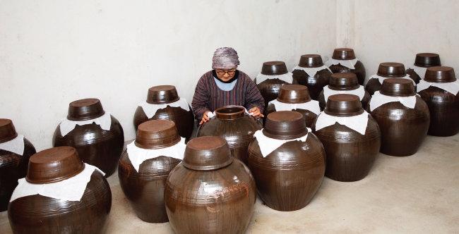 농장 저장창고에 보관된 30여 개의 매실초 항아리. 김태순 대표가 옹기 뚜껑을 열고 식초 상태를 확인하고 있다. [조영철 기자]