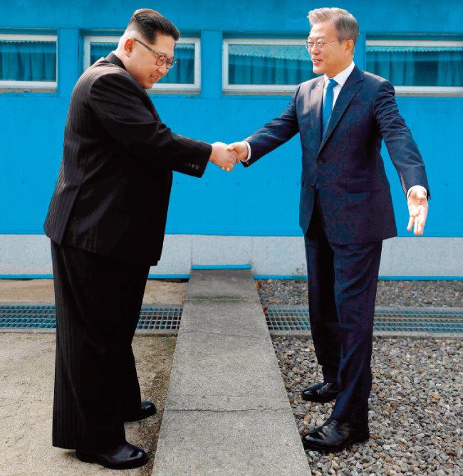 문재인 대통령과 김정은 북한 국무위원회 위원장이 4월 27일 오전 남북정상회담이 열리는 판문점의 군사분계선을 사이에 두고 악수하고 있다. [뉴스1]