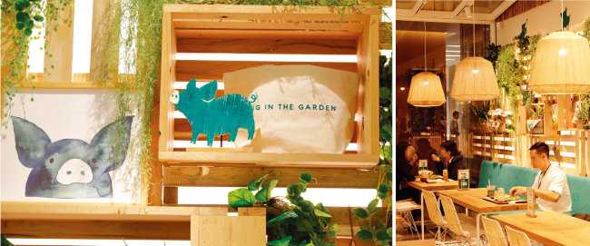 매장 곳곳에 그려진 초록 돼지의 표정이 평화롭게 느껴진다(왼쪽). '피그인더가든'에서 식사를 하고 있는 직장인들의 모습. [박해윤 기자]