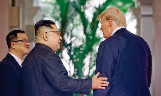 김정은 북한 국무위원장이 6월 12일 싱가포르 북·미 정상회담에서 처음 대면한 도널드 트럼프 미국 대통령의 왼팔을 잡고 친근감을 표시하고 있다. [사진 제공·싱가포르 정부]
