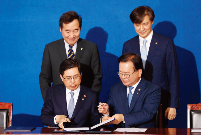 박상기 법무부 장관(앞줄 왼쪽)과 김부겸 행정안전부 장관(앞줄 오른쪽)이 6월 21일 정부서울청사 별관에서 검경 수사권 조정 합의문에 서명하고 있다. [동아DB]