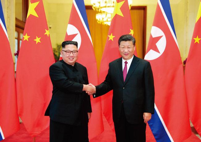 6월 19일 중국 베이징에서 김정은 북한 국무위원장이 시진핑 국가주석과 악수하고 있다. [뉴시스]