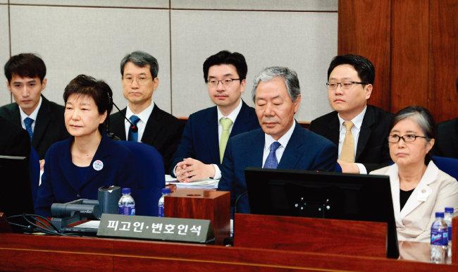 박근혜 전 대통령과 최순실 씨(맨 오른쪽)가 지난해 5월 23일 서울중앙지방법원 417호 대법정 피고인석에 이경재 변호사를 가운데 두고 나란히 앉아 있다. [공동취재단]