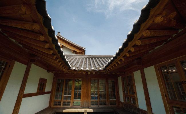 지상 1층의 ㄷ자 구조 툇마루. 처마지붕 너머 파란 하늘이 보인다.