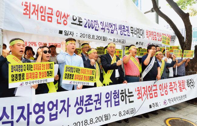 한국외식업중앙회 회원들이 8월 20일 오후 서울 종로구 광화문광장 인근에서 최저임금 인상 규탄 집회를 열고 자영업자 생계 대책 마련을 촉구하는 구호를 외치고 있다 [뉴시스]