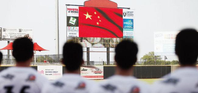 중국 야구 국가대표 선수들이 전체의 73%를 차지하는 텍사스 에어호그스 팀이 7월 18일 경기 시작 전 전광판에 뜬 중국 국기에 경례를 하고 있다. [뉴시스=AP]