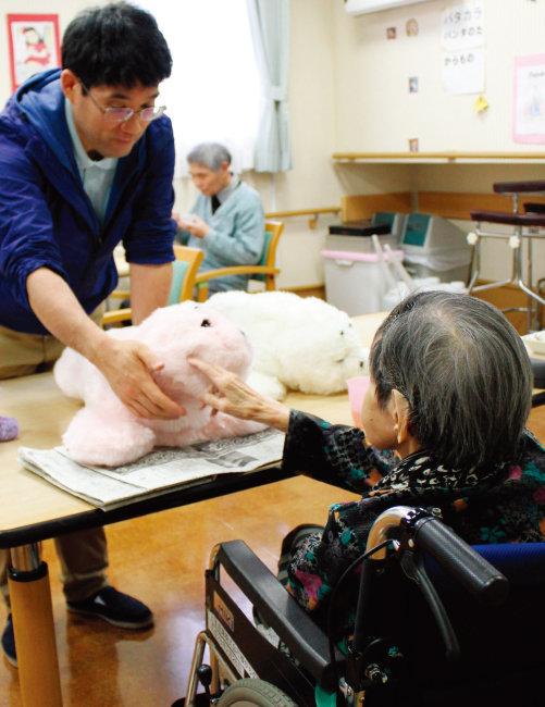 2017년 일본 한 요양시설에서 복지사가 로봇 인형을 이용해 노인을 치료하고 있다. [동아DB]
