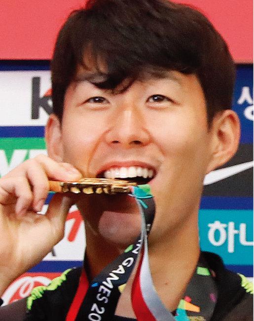 9월 3일 오전 인천국제공항을 통해 입국한 남자 축구대표팀 주장 손흥민이 금메달을 깨물며 포즈를 취하고 있다. [뉴스1]