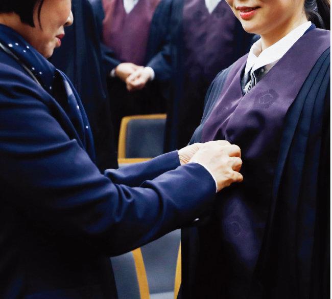 2017년 12월 서울 서초구 대법원에서 열린 '신임법관 임명식'에서 가족이 신임법관에게 법복을 입혀주고 있다. [뉴시스]