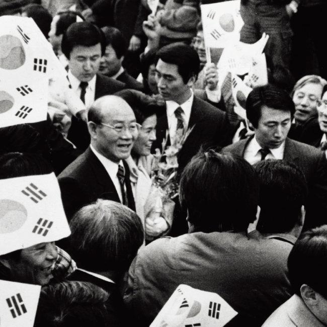 퇴임한 전두환 전 대통령 부부가 연희동 자택으로 돌아온 1988년 2월 25일, 주민들이 태극기를 흔들며 환영하고 있다. [동아DB]