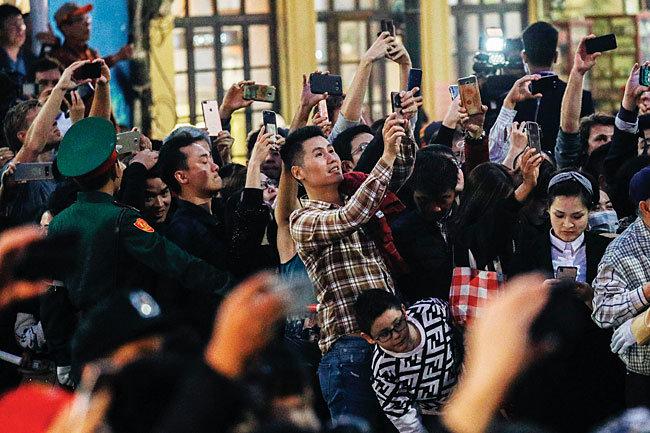 김정은 북한 국무위원장과 도널드 트럼프 미국 대통령의 저녁 만찬이 예고된 2월 27일 오후 베트남 소피텔 레전드 메트로폴 하노이 호텔 앞에서 베트남 시민들이 트럼프 대통령 차량 행렬을 사진에 담고 있다 [뉴시스]