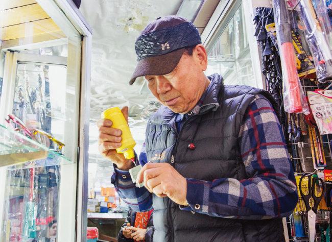 최영길 만물사 대표가 지포 라이터에 기름을 넣고 있다. [김도균]