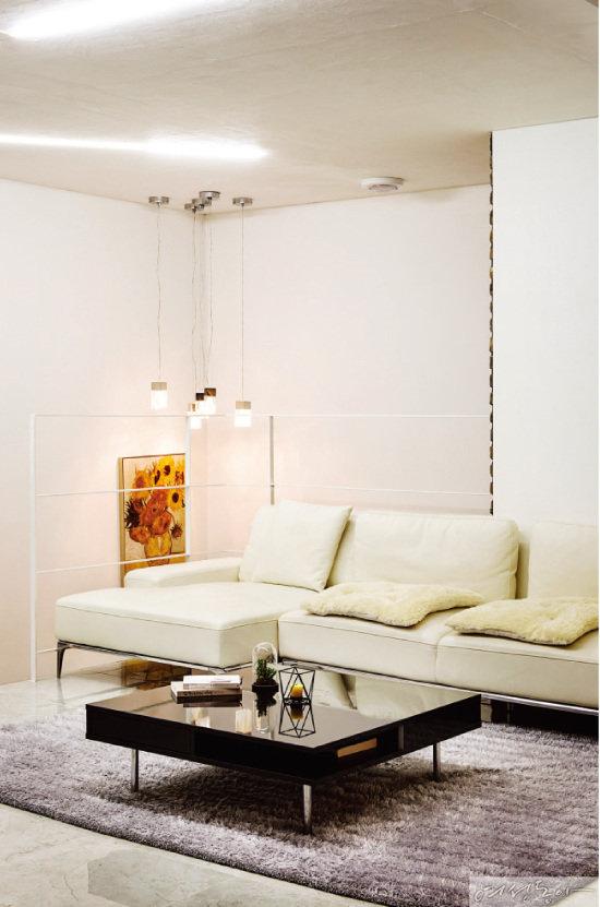 화이트 소파와 카펫으로 꾸민 2층의 거실. 천장에 일자형 LED 조명을 매입하고, 드롭형 조명을 여러 개 달아놓으니 리듬감이 더해진다.