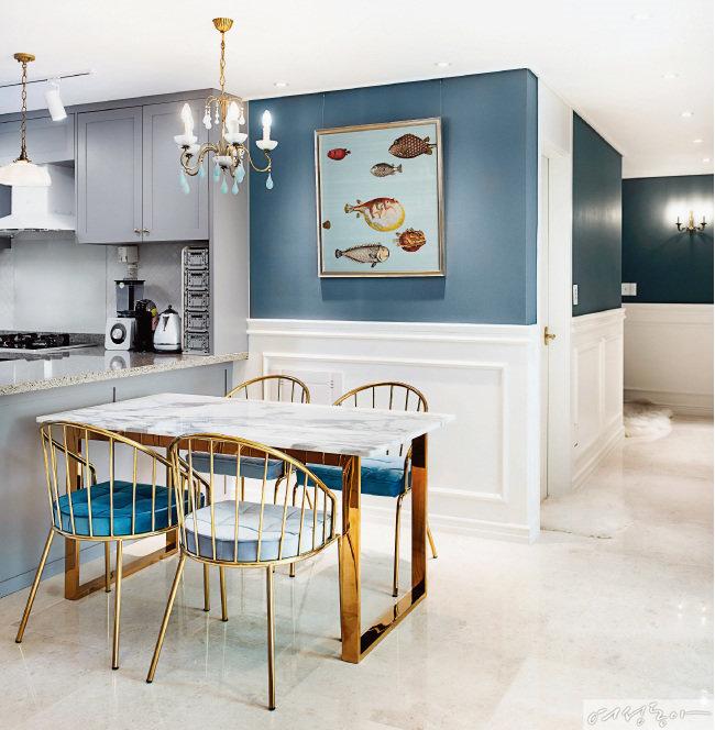 골드와 블루, 그레이 컬러로 우아함을 강조한 다이닝룸.  골드 프레임 식탁과 의자로 세련된 느낌을 낸 뒤 에메랄드빛 샹들리에와 물고기 그림 액자로 위트까지 더했다.