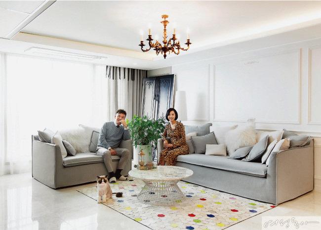 모던한 대리석 타일 바닥과 웨인스코팅 장식 벽, 클래식한 샹들리에가 어우러져 모던 프렌치 스타일 거실을 완성했다. 레드, 그린, 옐로 컬러가 믹스매치된 카펫이 리듬감을 준다.