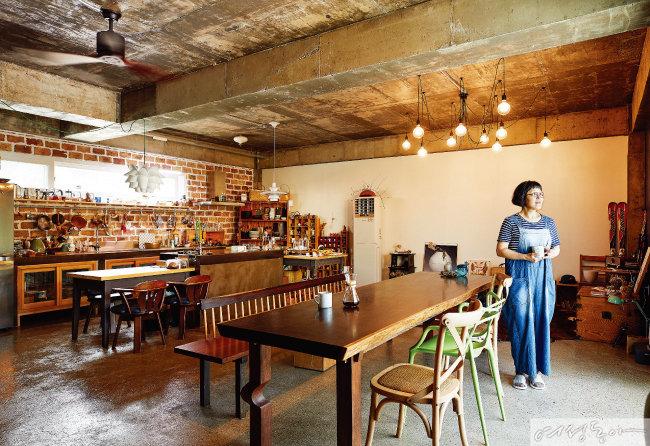 노출 콘크리트 천장과 붉은 벽돌로 인더스트리얼하게 연출한 1층. 20평 남짓한 공간을 나누지 않고 주방이자 다이닝룸, 거실로 사용하고 있다. 태국 도예가 친구에게 선물 받은 실링팬이 이국적인 분위기를 더한다.