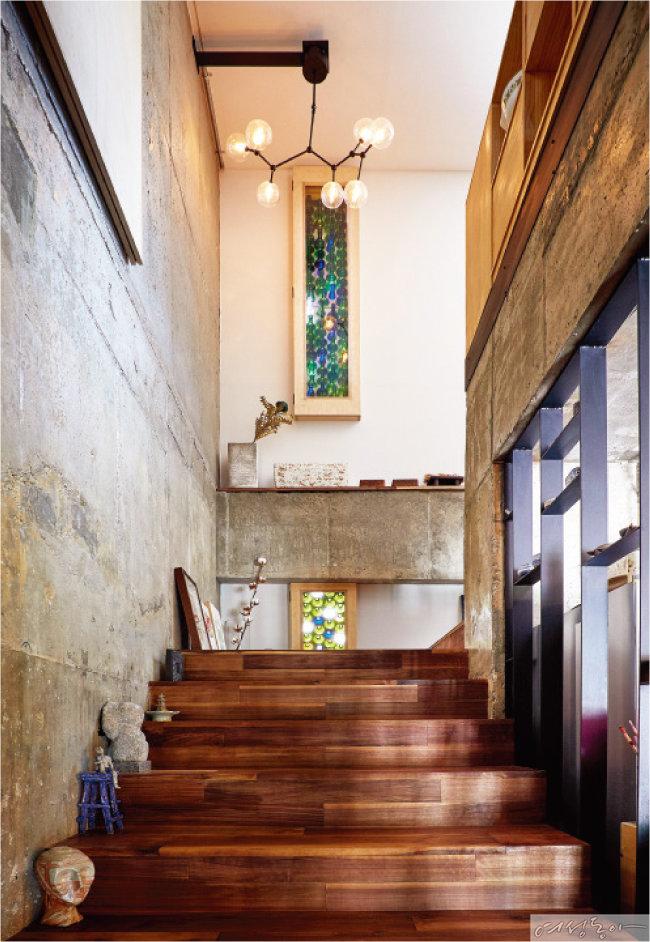 강화수 작가가 원목으로 직접 만든 계단은 밟을 때마다 온기가 느껴진다. 와인 애호가인 부부는 그동안 마시고 모아둔 와인병을 활용해 '와인 스테인글라스 창'을 만들었다.